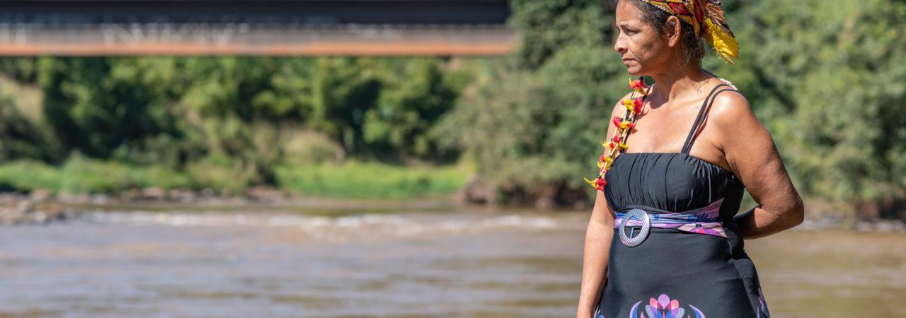 A pajé Angohó Ha-ha-hãe, uma das líderes da aldeia indígena Naô Xohã, posa para uma foto próximo ao rio Paraopeba. A comunidade Naô Xohã está solicitando à Vale sua realocação temporária devido à poluição do rio. Imagem: cortesia de Luiz Guilherme Fernandes para Mongabay
