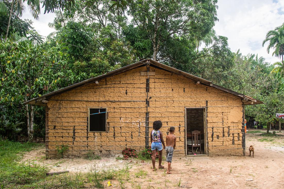 Duas pessoas e um cão em frente de uma casa em uma comunidade quilombola.