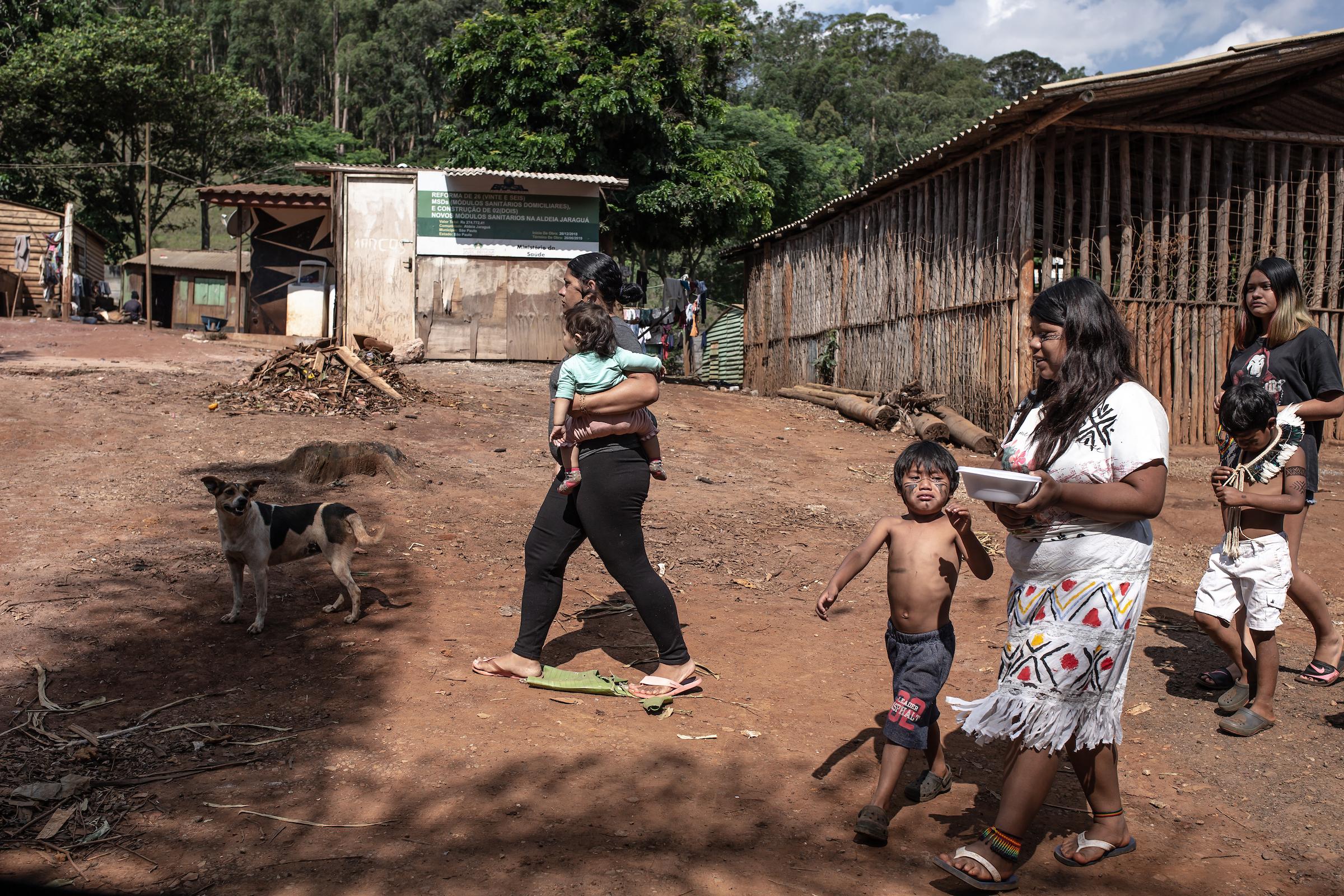 Adults and children walk through a village.