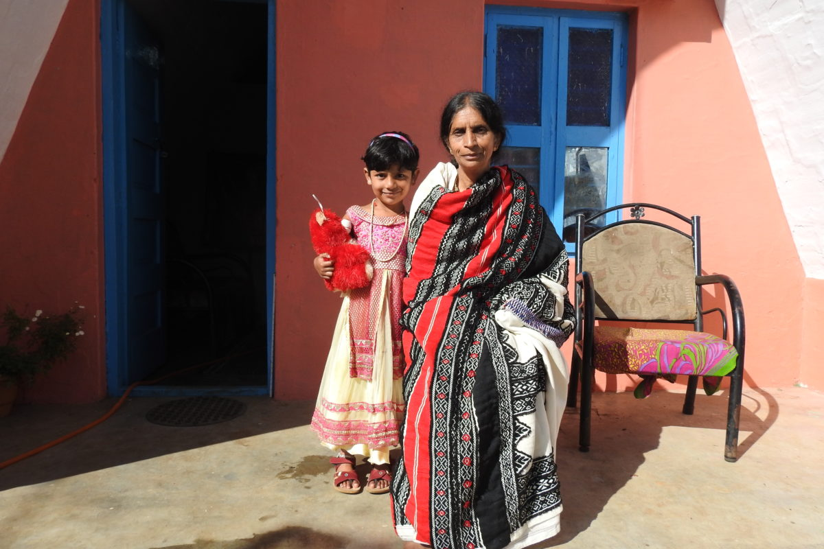 Vasamalli Kurtozen, is a State Wildlife Board member and the first Toda woman to earn a post-graduate degree. Pictured in front of her home with her granddaughter. Photo by Bhanu Sridharan.