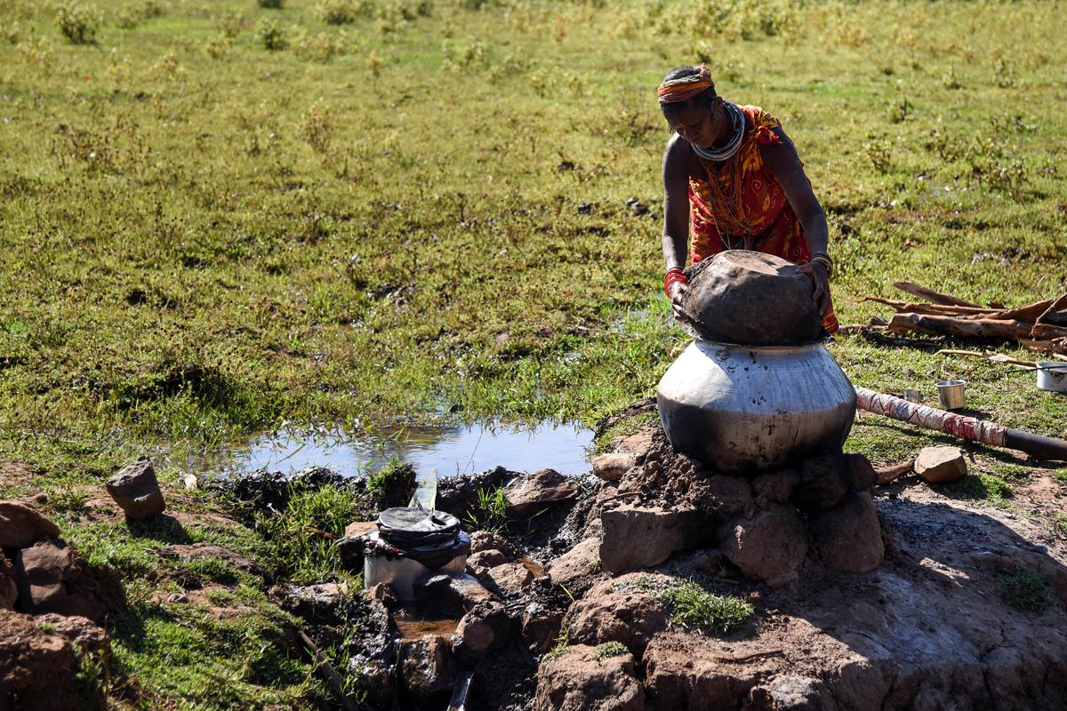 A Bonda woman preparing liquor from millets at Bonda hill.