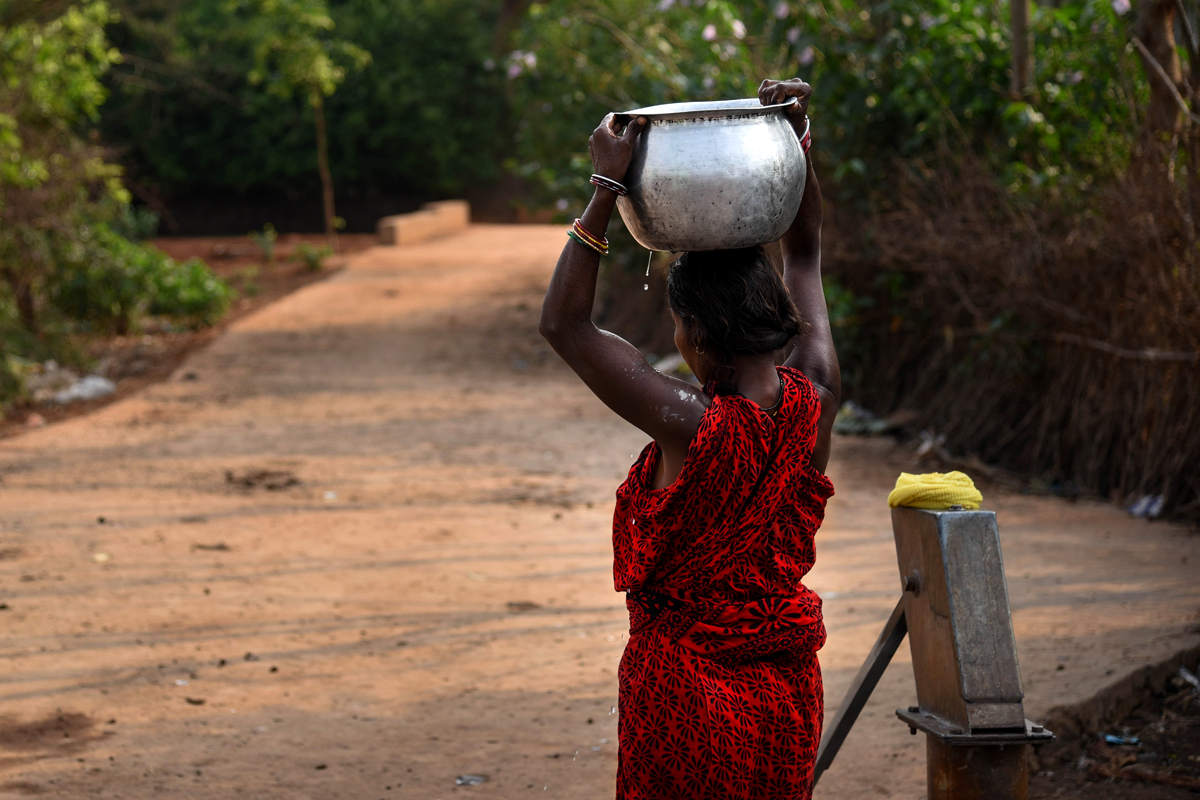 A woman carries drinking water from a tube well at Malichema, a village affected by mining activities. Credit: Tanmoy Bhaduri/MongaBay