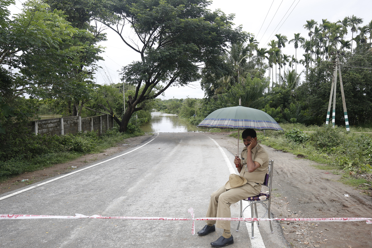 A policeman maintains vigil as the Cauvery river flows over a road on the outskirts of Kushalnagar. Photo by Abhishek N. Chinnappa.