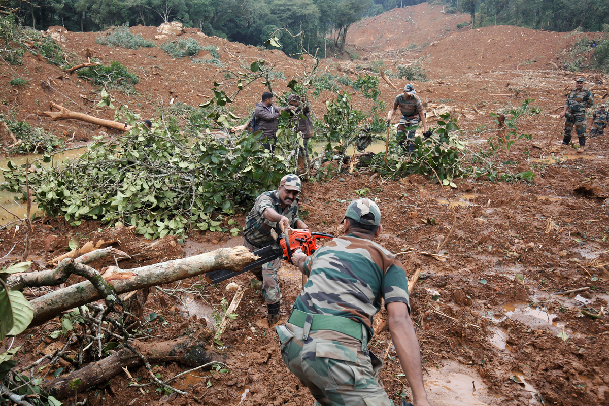 Army soldiers look through debris at the site of a landslide in Thora village, Kodagu. Photo by Abhishek N. Chinnappa.