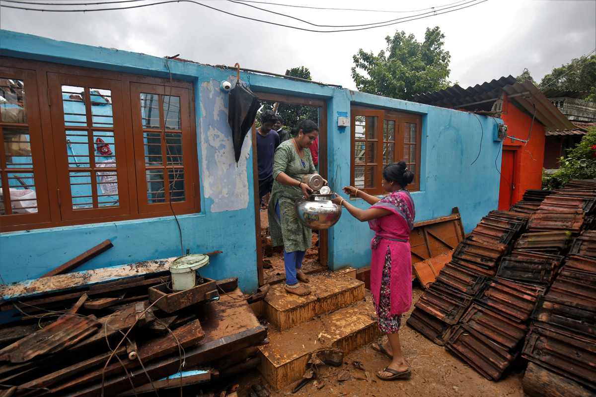 People salvage utensils and other belongings from a house destroyed by the flood. Photo by Abhishek N. Chinnappa.