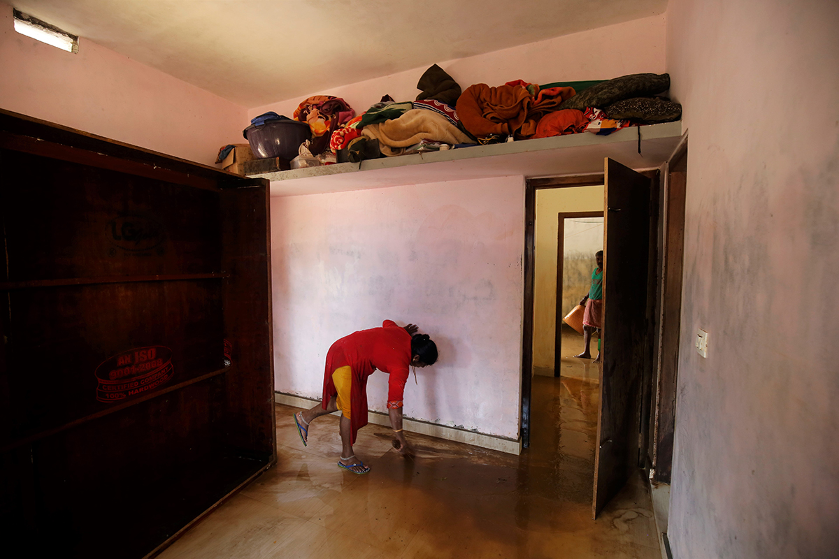 A woman cleans her house after the floodwaters of Cauvery retreated. Photo by Abhishek N. Chinnappa.