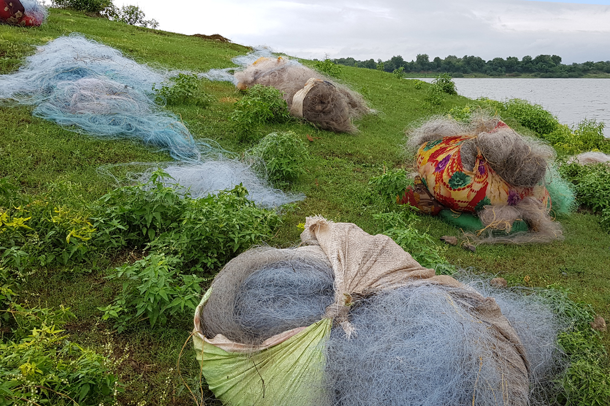 Excessive mud and thorny bushes dumped in the river by sand miners damage fishing nets. Photo by Hridayesh Joshi.