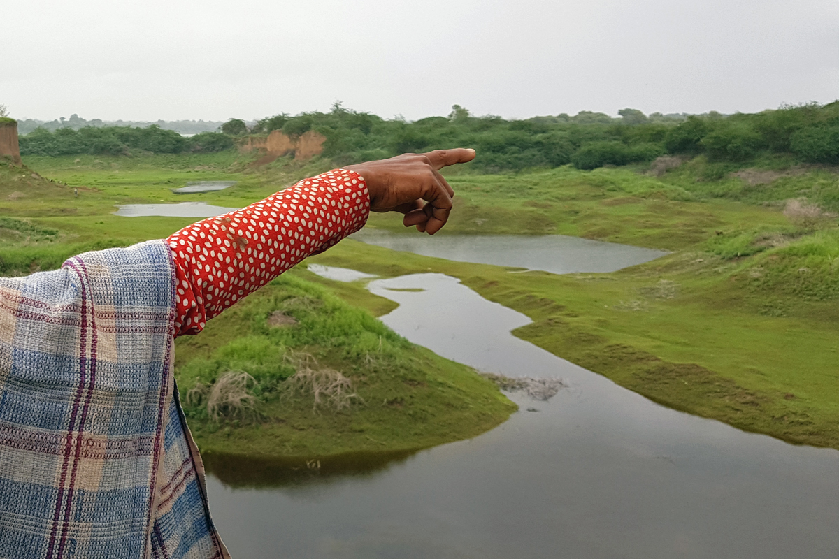 A villager points to land on the banks of the Narmada which was once rich with different crops before it was dug for sand mining. Photo by Hridayesh Joshi.
