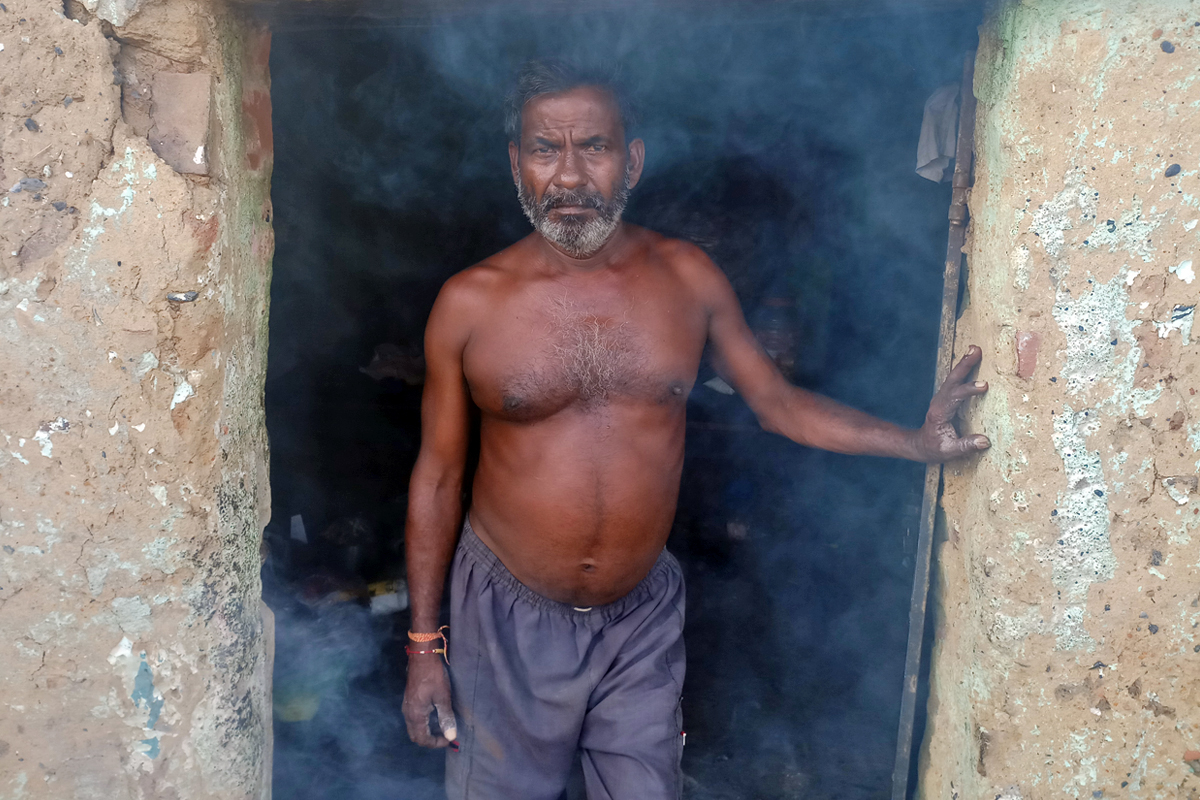 Manoj Ramani, 48, at his residence surrounded by smoke released from the mines. A plan to relocate people to safer areas has moved at a snail's pace, with a mere 3,000 families out of 140,000 rehabilitated to a nearby township. Photo by Gurvinder Singh.