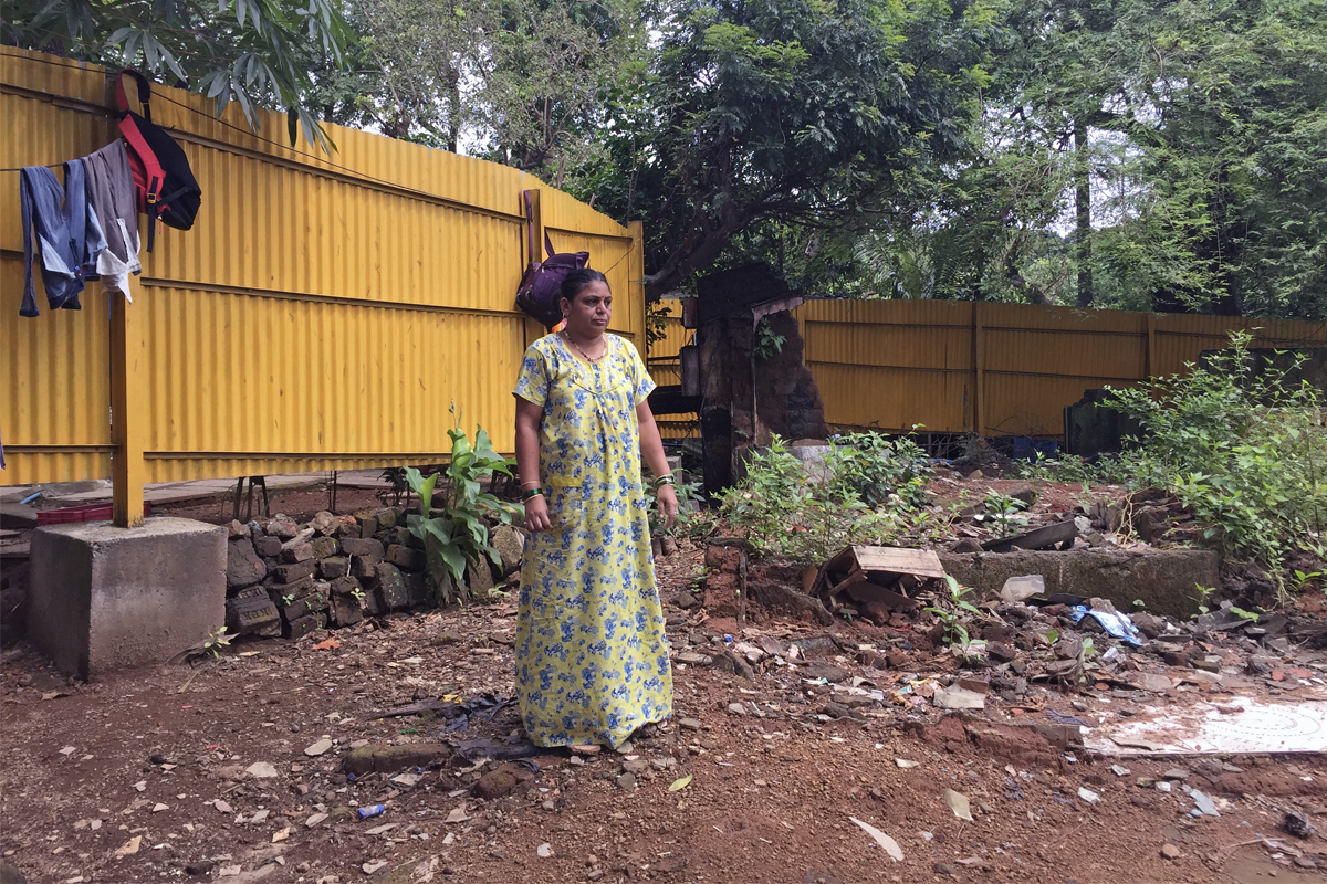 Asha Bhoye, a member of a tribal community residing inside Aarey, stands in front of the barricade raised by the authorities in front of her house. Photo by Kartik Chandramouli/Mogabay.