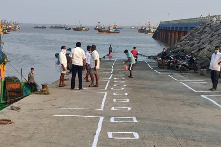 Fishworkers create markers to ensure social distancing while working on a port along Maharashtra's coast. Photo by Ganesh Nakhawa.