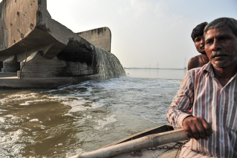 A fisherman rows past a wastewater outlet on the Ganges river near Kanpur. Air and water pollution have been shown to add a significant cost to India's GNP. Photo by Neil Palmer (IWMI).