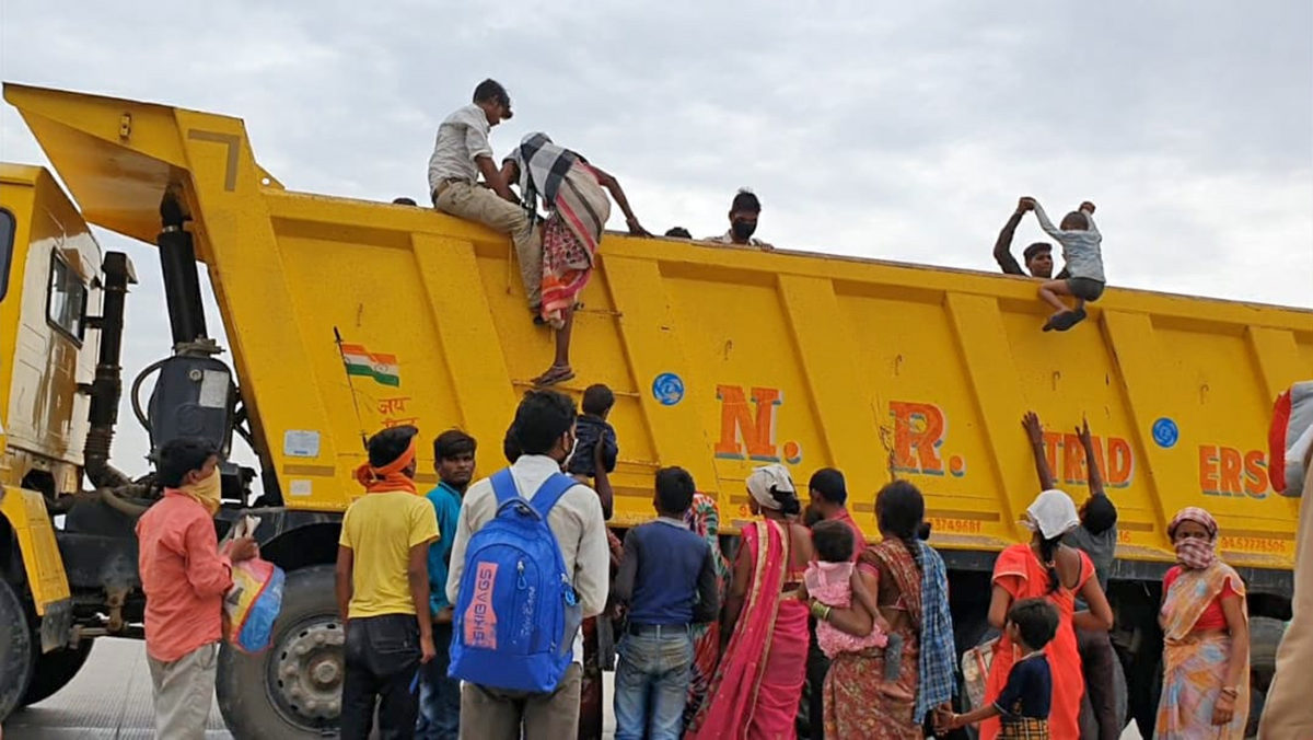 Migrants in Uttar Pradesh try to board a truck in an attempt to return to their homes during the COVID-19 lockdown. Photo by Ravish Ranjan Shukla.