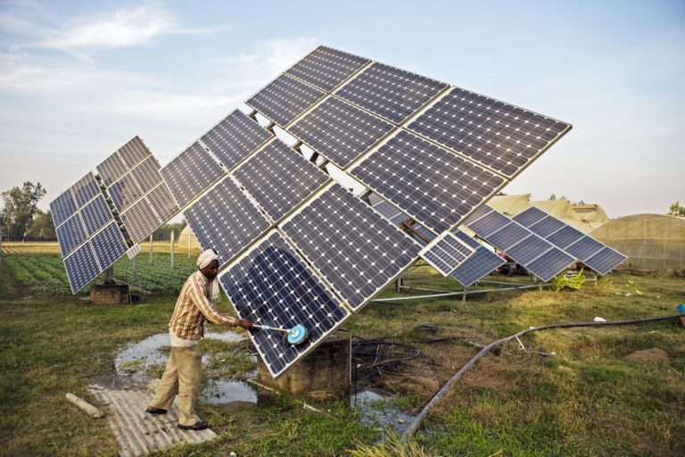A farm worker cleans solar panels of a solar water pump. Photo by Prashanth Vishwanathan (IWMI)/Flickr.