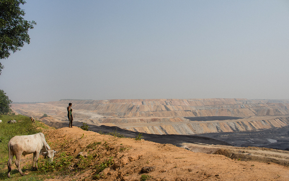 A pastoralist looks at Hasdeo's Parsa East and Kete Basan (PEKB) mine that has lead to severe environmental and social issues. Residents of Hasdeo region fear their land meeting the same fate as its adjacent Korba, a critically polluted area. Photo by Vaishnavi Suresh.