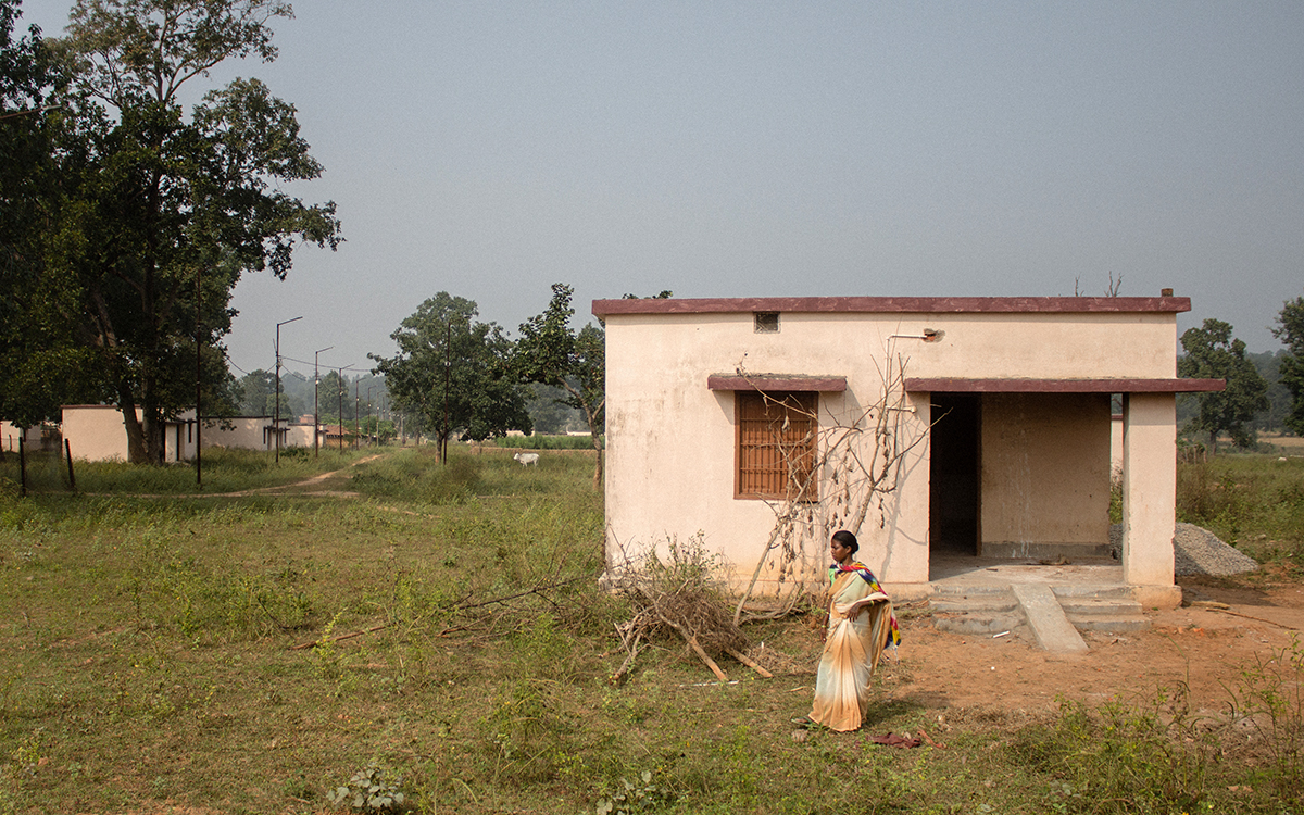 A native of Parsa village stands in front of her house built in exchange for the land acquired by PEKB coal mines. The cluster of resettlement houses lacks electric connections. Photo by Vaishnavi Suresh.