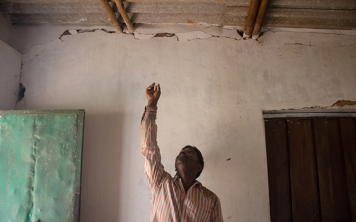 Ramlal, whose lives adjacent to Gevra coal mine, points at the cracks in his house caused by continuous blasting in the mine. Photo by Vaishnavi Suresh.