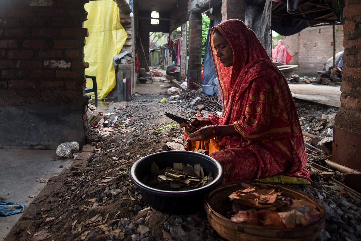 Rakima Bibi rolls beedis at her temporary house in Dhanghara. Samserganj is a popular hub for the beedi industry in the state. Bibi demolished her own house and sold the materialto minimise her losses. Photo by Tanmoy Bhaduri.