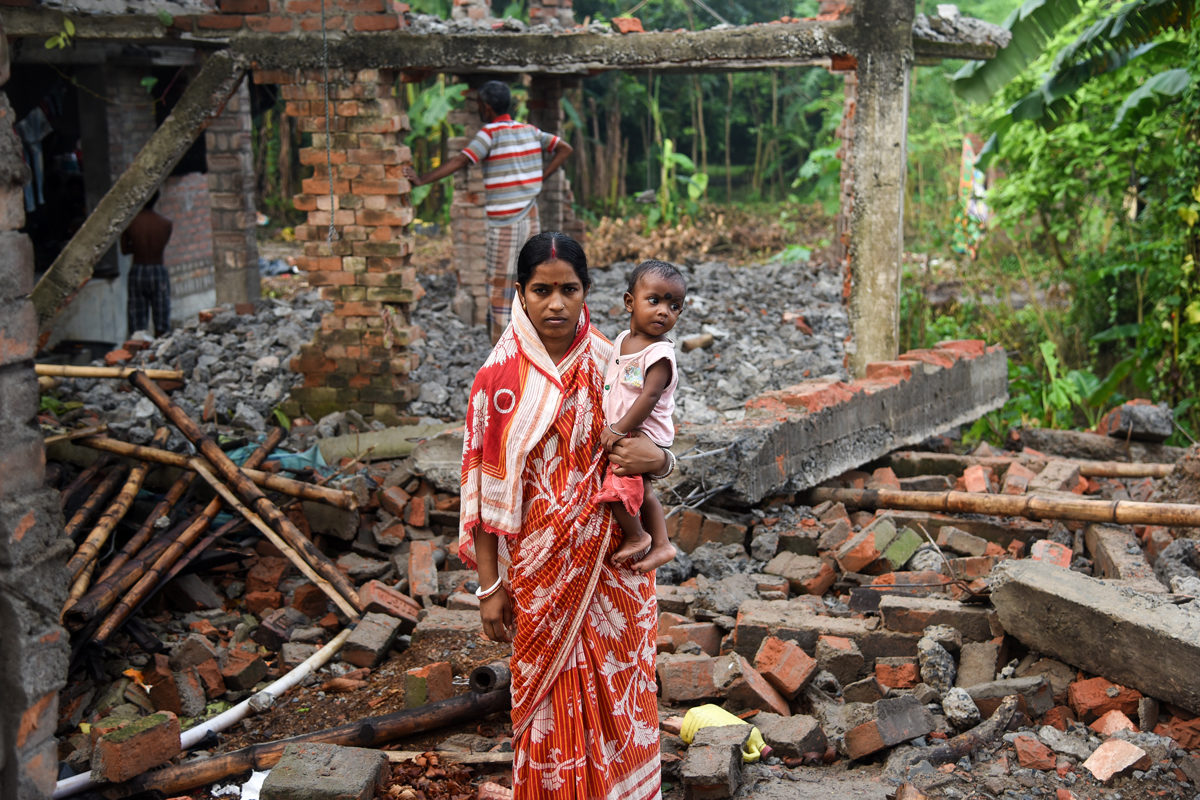 """Sampa Mondal with her child amidst houses that were dismantled from fear of erosion and floods. Her house in Dhanghara was destroyed and herfather's house inNatun Shibpur met the same fate. """"The erosion is so fast in the region. Where should we go now?"""" she asked. Photo by Tanmoy Bhaduri."""