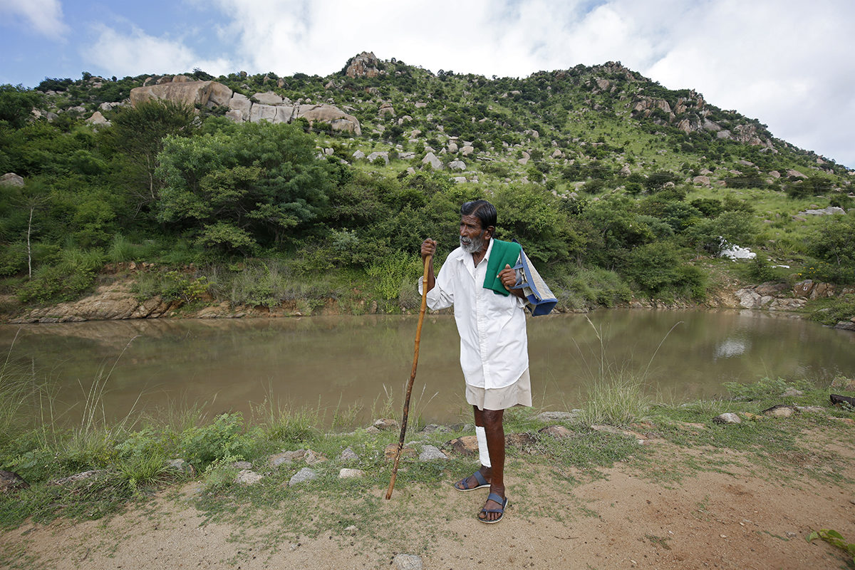 Kalmane Kaamegowda or the 'pond man' in front of one of the 16 ponds he dug in his village in Mandya, Karnataka. The wetlands have become a source of water for wild animals and livestock. Photo by Abhishek N. Chinnappa.
