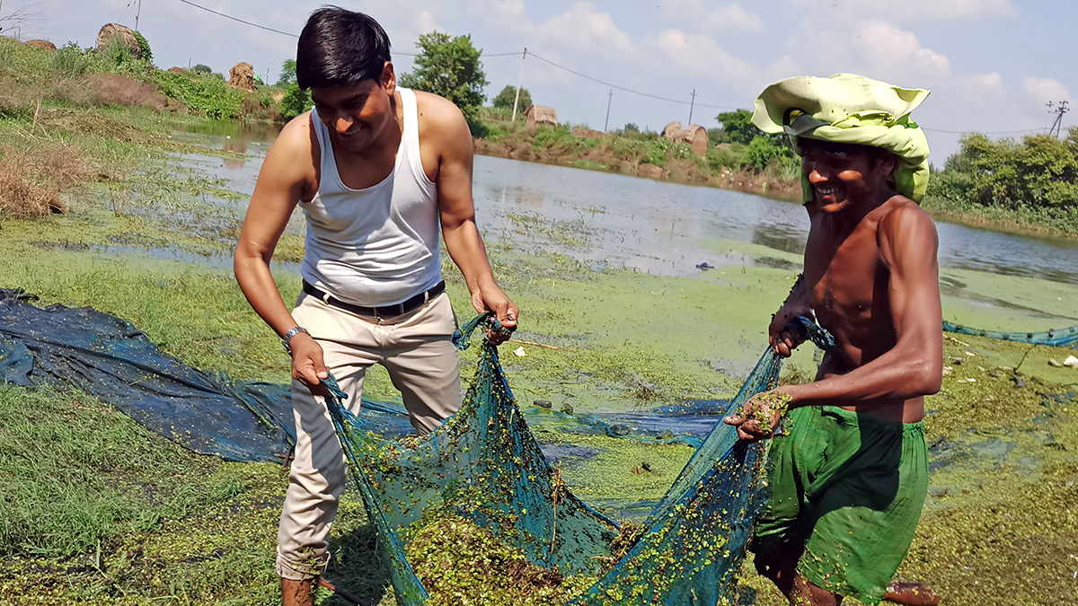Ramveer Tanwar (left) cleaning the pond at Azampur Garhi village. Photo from Ramveer Tanwar.