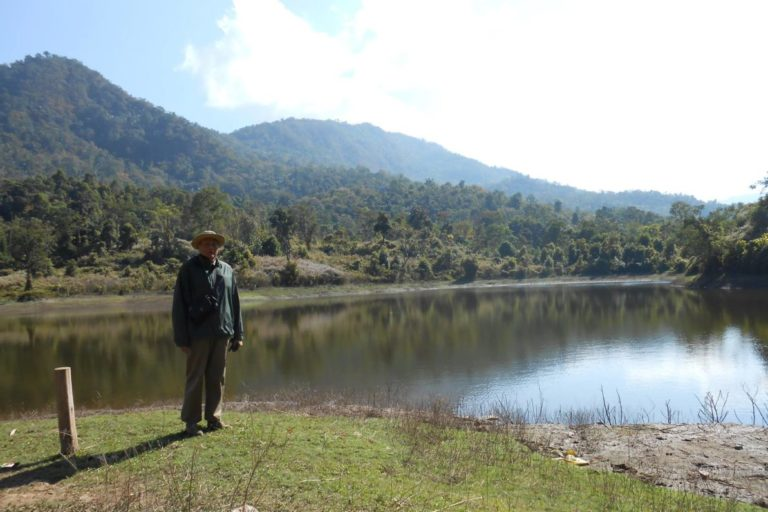 Gwasinlo Thong, chairperson of the reserve committee in front of the Nsonji Lake, Sendenyu Community Biodiversity Reserve. Photo from Sendenyu Community Biodiversity and Wildlife Reserve.