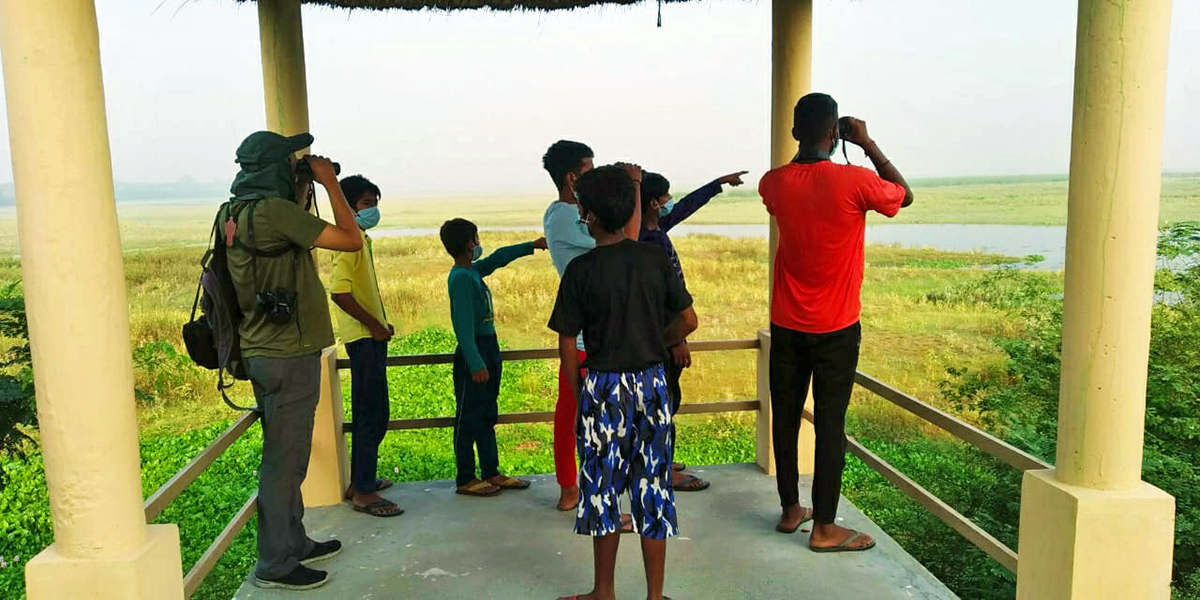 Ashish Loya (left) birdwatching in Haiderpur with the youth from the local community. Photo from Ashish Loya.