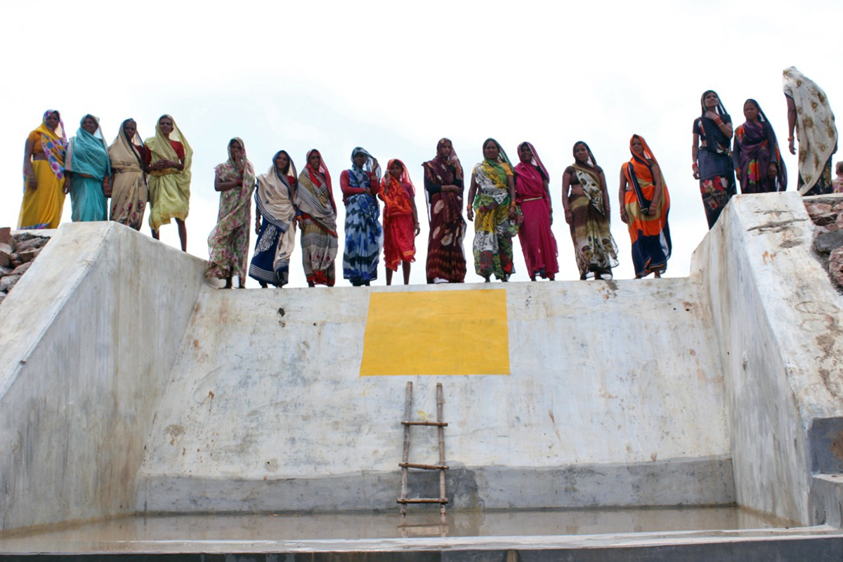 The women of Chaudhary Khera village stand on the check dam they built while restoring the Baba Talaab. Photo from Parmarth Samaj Sevi Sansthan.