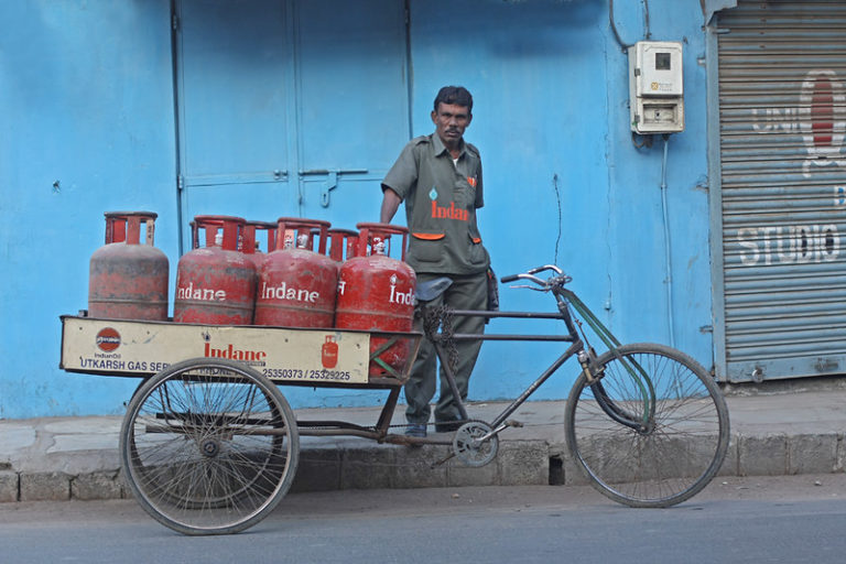 A vendor carrying LPG cylinders