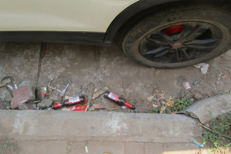 Empy alcohol glass bottles near a parked vehicle in a Goa beach. Photo by Pamela D'Mello.