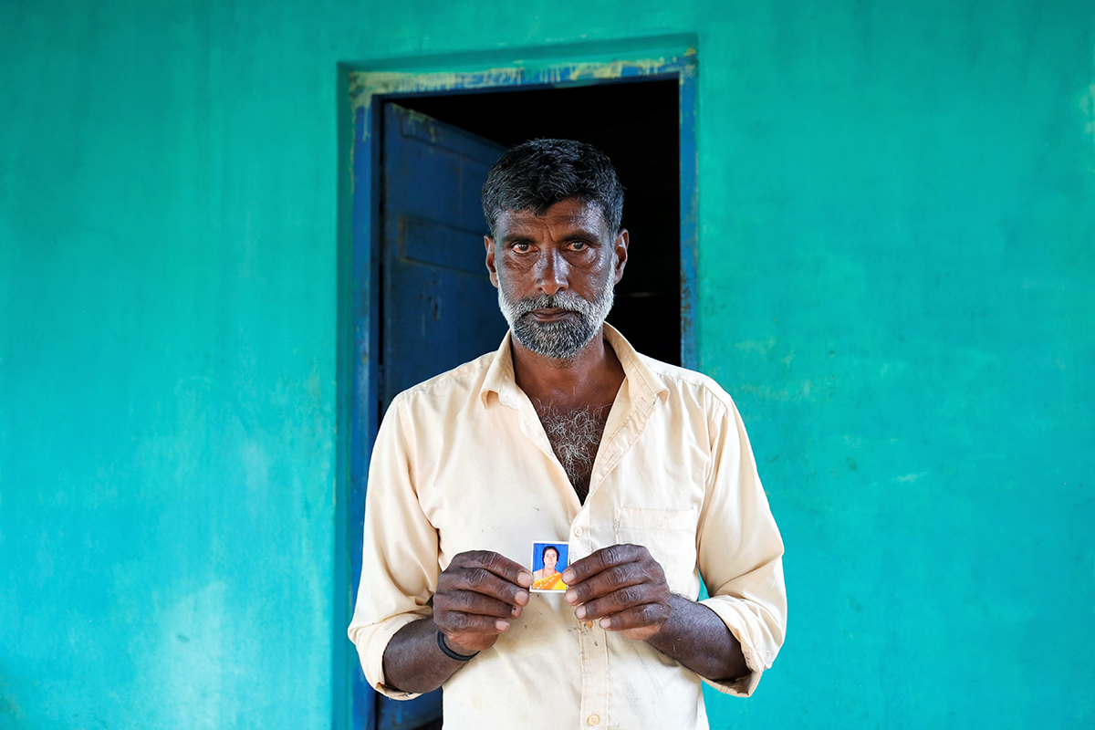 Ganesh VS, 51, husband of Sujata, 40, poses with her photo in Chowdikatte village. Sujata died due to renal failure caused by complications following a bite from Russell's viper. Photo by Abhishek N. Chinnappa.