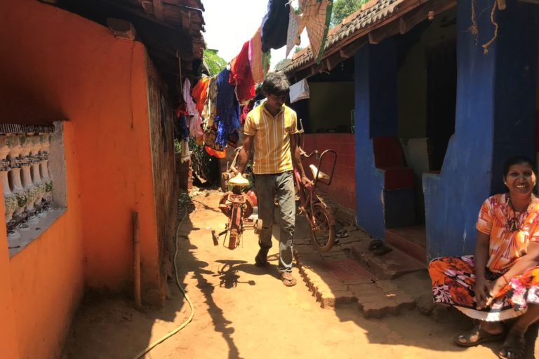 A man carries a child's cycle to the playground in mining-affected Sonshi village in north Goa. Photo by Supriya Vohra.
