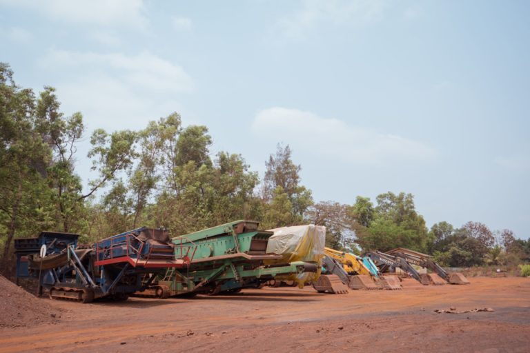 A parking lot for mining machinery, next to the primary school in Sonshi village. Photo by Neil D'souza.