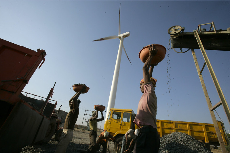 Workers working at a diesel-powered crusher in front of a wind turbine. India's energy transition could mean greater conversion from agricultural lands, biodiversity-rich lands or lands earmarked for other development activities. Photo by Land Rover Our Planet/Flickr.