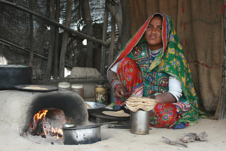 A woman cooking Chapatis in a small village in the Kutch, Gujarat, India. GoI launched a scheme named PMUY in 2016 with the purpose of giving LPG connection to families falling under Below Poverty Line (BPL). Majority of villagers got LPG connections but usage is quite low. Photo by Chris/Flickr
