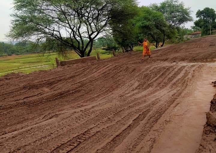 A woman finds it tough to walk on a dilapidated road in the Hemgir block of Sundergarh district in Odisha. By special arrangement.