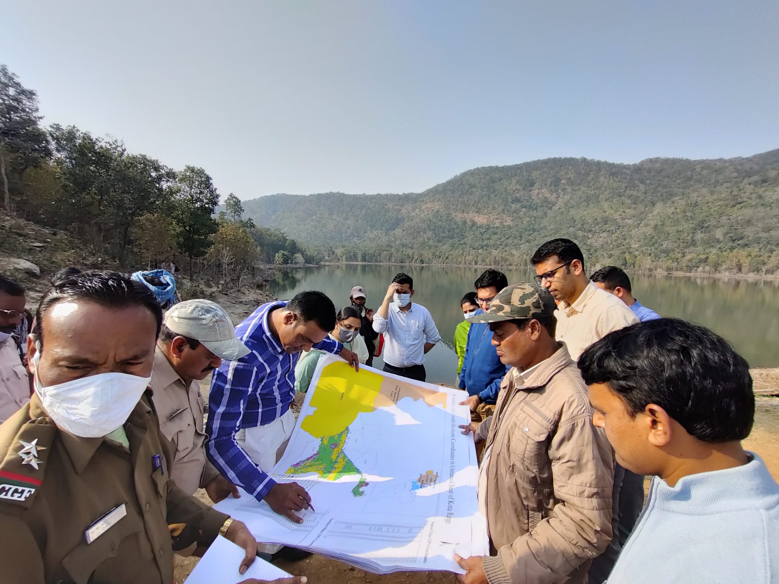 Forest officials inspect a map during a field visit in Kota range of Bilaspur district