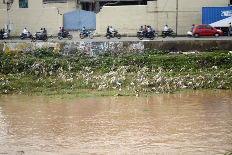 Noyyal River in Tamil Nadu lined with plastic waste. As urban India aspirations grew, so did our appetite for consumption and desire for profits. The middle class increasingly became disconnected from their own ecological footprint. Photo by PJeganathan/Wikimedia Commons.
