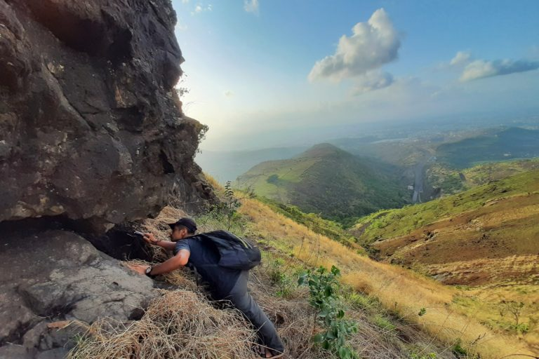 Shubhankar Deshpande examining rock crevices to look for scorpion specimens. Photo by Anuj Shinde