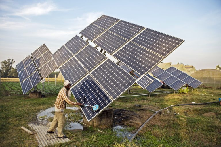 A farmworker cleans the solar panels of a solar water pump at the farm. Photo by Prashanth Vishwanathan (IWMI)/Flickr.