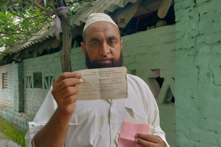 Shamsher Ali of the Van Gujjar community posing with a fee slip for taking his cattle to graze in the forest. Photo by Nishant Saini.