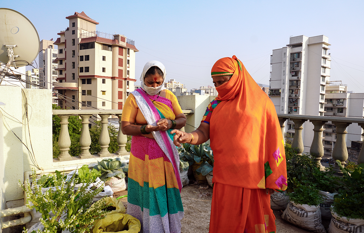 Noor Jahan Syed and Sushila Ahire, employed with Stree Multi Sangathan (SMS), learn from a terrace garden of a housing society in the eastern suburb of Chembur. Syed points out that only those with enough space can grow their own food in the city; while others cannot. Photo by Prateek Pamecha.