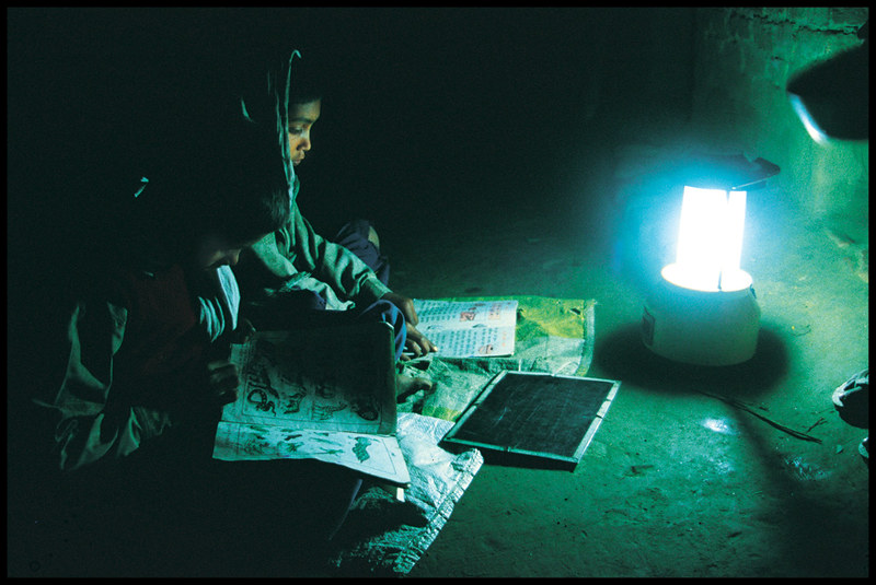 A woman studying while using a solar lantern. Photo by Barefoot Photographers of Tilonia/Flickr.