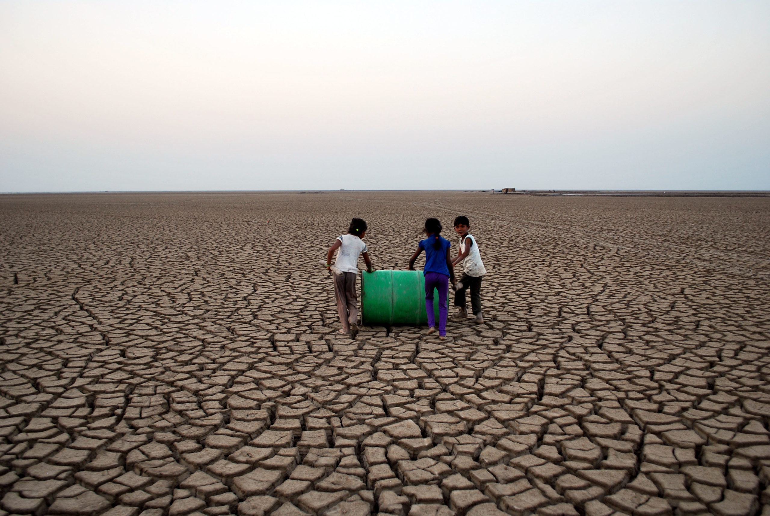 The children of the Agariya community playing with a barrel of oil in the cracked topography of the Little Rann. Photo by Dhvanit Pandya/AHRM.