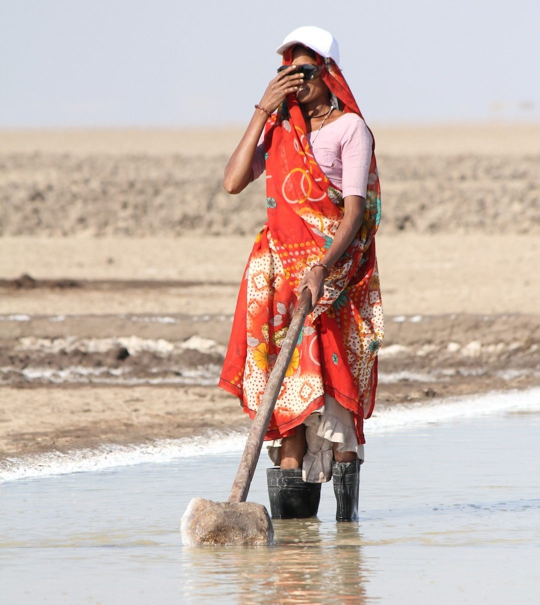 An Agariya woman working in the salt pan with safety gears like shades, gum boots and caps provided by the NGOs to avoid the harsh sun and salt water. Photo by Dhvanit Pandya/AHRM.