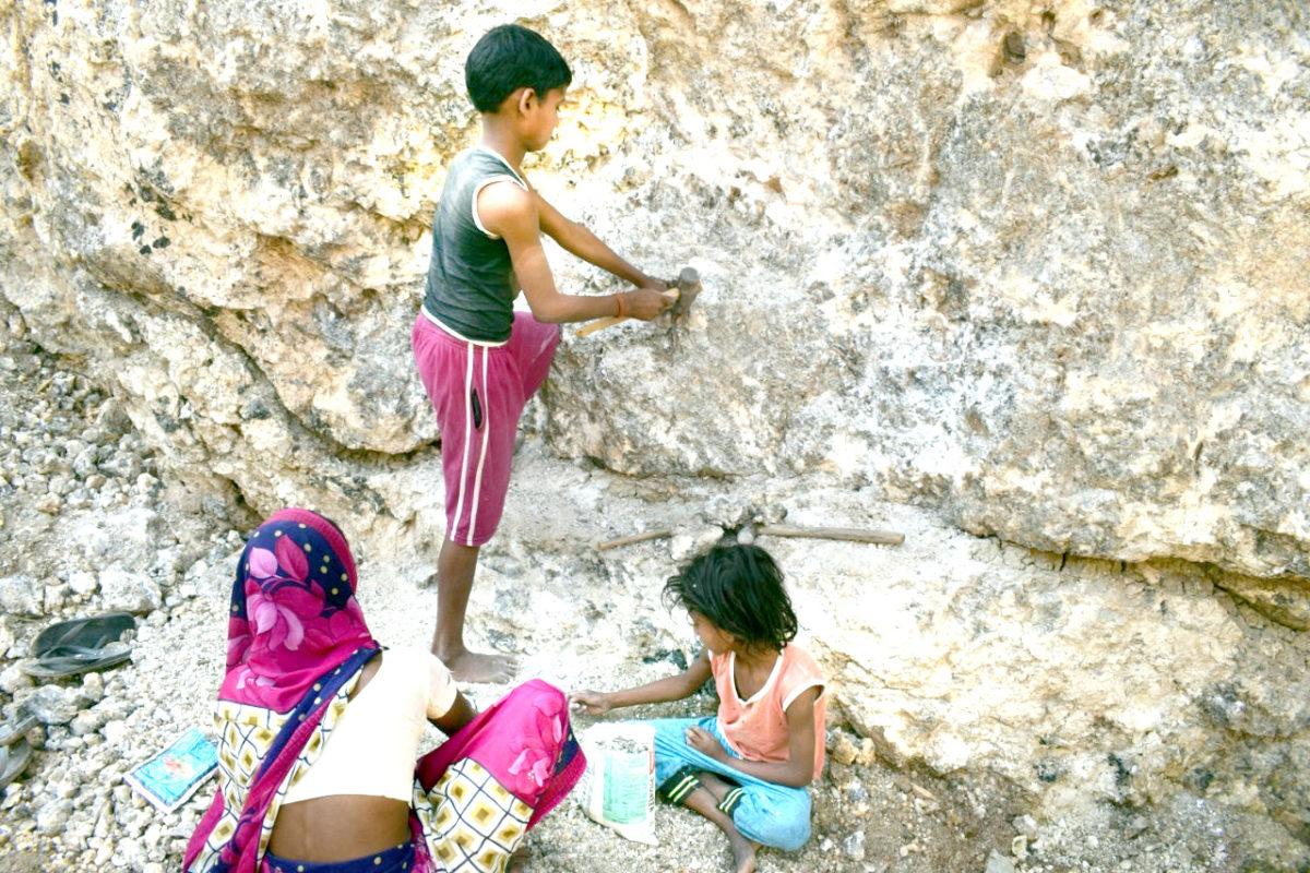 झारखंड के कोडरमा जिले के तिसरी तहसील में परित्यक्त खदान से महिला अपने बच्चे के साथ ढिबरी निकाल रही है। फोटो- विनय मुरमू