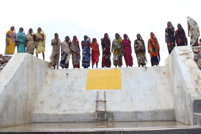 बड़ा तालाब पर बने चेक डैम पर महिलाओं की टोली खड़ी है। इन्होंने कड़ी मेहनत से इस तालाब को नया जीवन दिया है। तस्वीर- परमार्थ समाजसेवी संस्थान