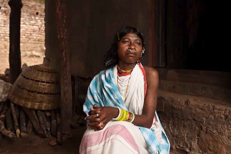 तीस वर्ष की गात्री कादराका पारंपरिक डोंगरिया वस्त्रों में घर के सामने बैठी हुई हैं। तस्वीर- इंद्रजीत राजखोवा