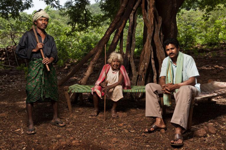 हुंडिजाली गांव में ड्रम्बु जाकेसिका, बेजुनी कुमताबी सिकोका और बारिक संयासी टाकरी पेड़ के नीच बैठे हुए हैं। तस्वीर- इंद्रजीत राजखोवा
