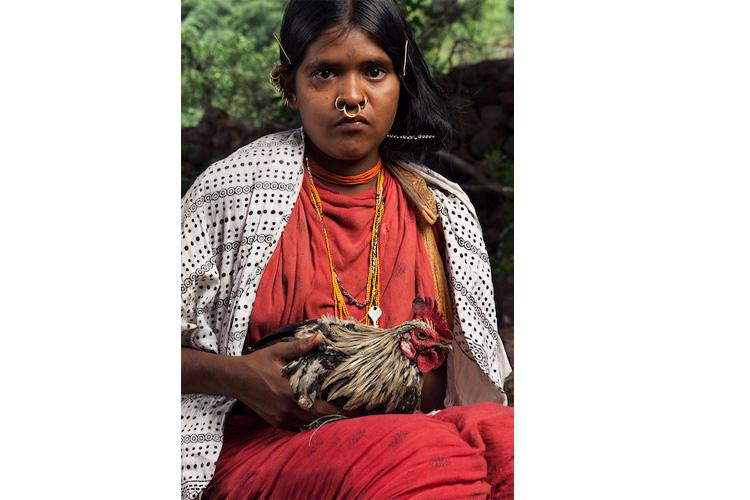 हाथ में मुर्गी के साथ हुंदिजाली गांव में एक डोंगरी लड़की। यहां जरूरत की चीजों के लिए आज भी बार्टर्ड सिस्टम (सामान के बदले सामान) की परंपरा कायम है। तस्वीर- इंद्रजीत रखोवा